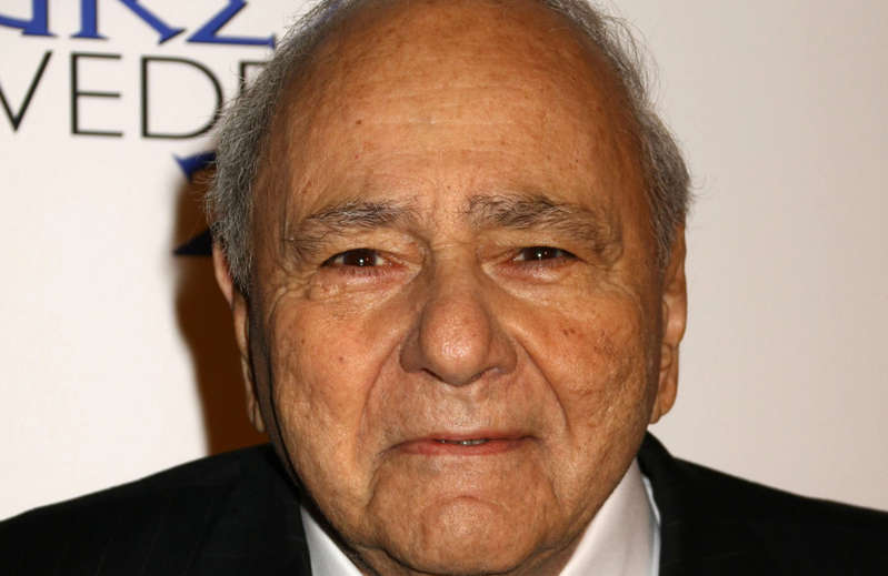 Michael Constantine wearing a suit and tie smiling at the camera