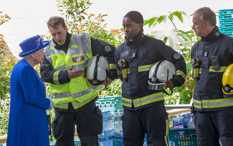 Nathan Dyer et al. holding wine glasses: Her Majesty meeting members of the emergency services following the Grenfell Tower fire in 2017 - Eddie Mulholland for The Telegraph