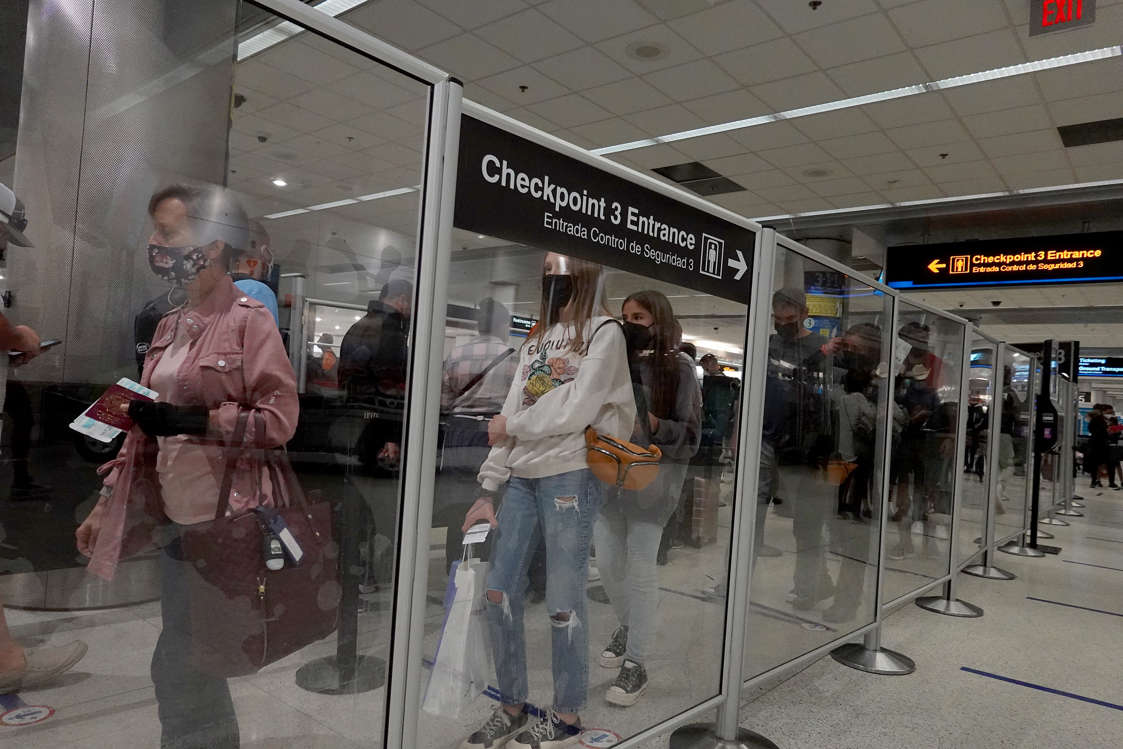 a group of people standing in front of a store: Travelers wait in line at the TSA checkpoint at Miami International Airport before Labor Day weekend. (Joe Raedle/Getty Images)