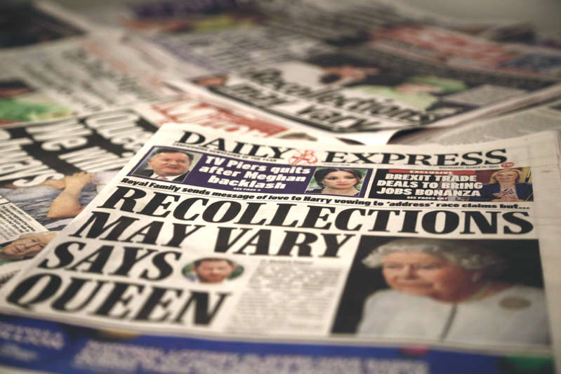 File: An arrangement of UK daily newspapers shows front page headlines reporting Queen Elizabeth's respond over the interview given by the Duchess of Sussex, Meghan Markle and her husband Britain's Prince Harry, Duke of Sussex, to media mogul Oprah Winfrey about their experiences with Buckingham Palace, in London, United Kingdom on March 10, 2021. (Photo by Hasan Esen/Anadolu Agency via Getty Images)