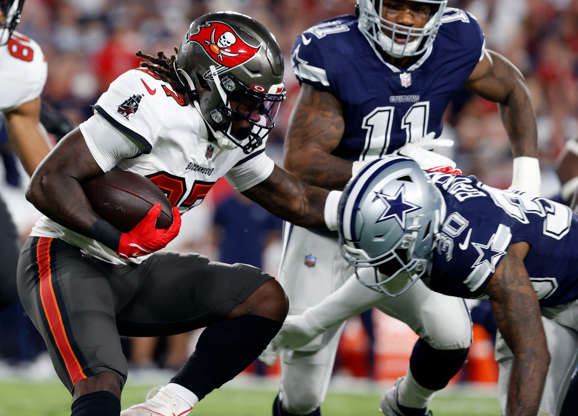 Slide 4 of 11: Tampa Bay Buccaneers running back Ronald Jones (27) runs the ball against the Dallas Cowboys.