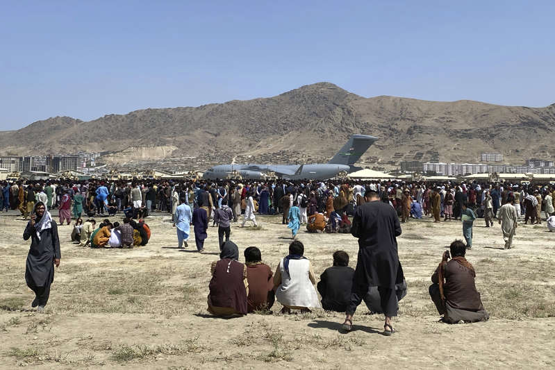 a group of people standing on top of a mountain: A large crowd gathers near a U.S. Air Force C-17 plane at the perimeter of Kabul airport on Aug. 16.