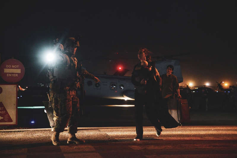 a group of people standing around a fire: A Marine escorts a State Department employee to be processed for evacuation at the airport in Kabul on Aug. 15.