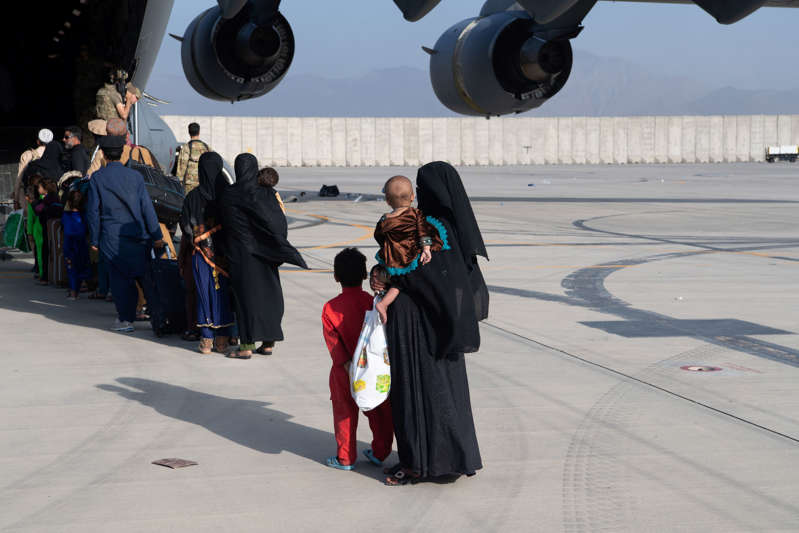 a group of people standing around a plane: U.S. Air Force members load passengers onto a C-17 Globemaster III at Kabul airport on Aug. 24 as part of the largest airlift evacuation of civilians in American history.