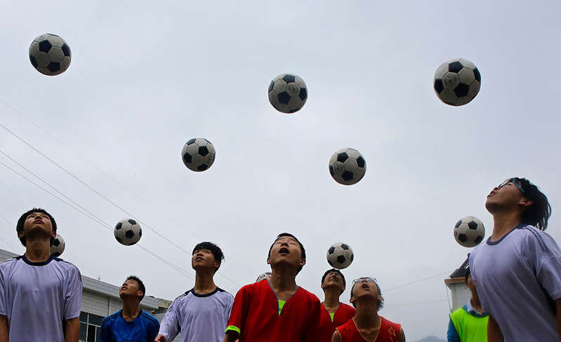 a group of people standing next to a football ball: Chinese students are seen during a football training session in the campus of the Yuyang Middle School in Wufeng Tujia Nationality Autonomous County of Yichang on June 1, 2016, in Hubei province, China. | Getty Images—2016 Wang He