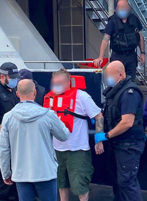 a group of people posing for the camera: A man being taken off the Jamaican-flagged yacht Kahu at an undisclosed location (NCA/PA)