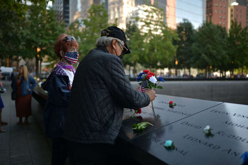 """a couple of people that are standing in the street: An Iranian newspaper published a """"questionable"""" cartoon on 9/11, calling the terrorist attack """"the beginning of America's end."""" Here, family members leave flowers the National 9/11 Memorial and Museum during the commemoration the 20th anniversary of the 9/11 attacks on the World Trade Center, in New York, on September 11, 2021."""