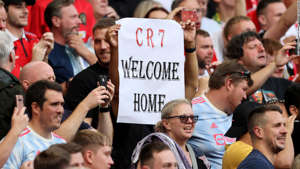 a group of people standing in front of a crowd: A fan holds aloft a 'CR7 Welcome Home' sign up during the match between Manchester United and Newcastle.