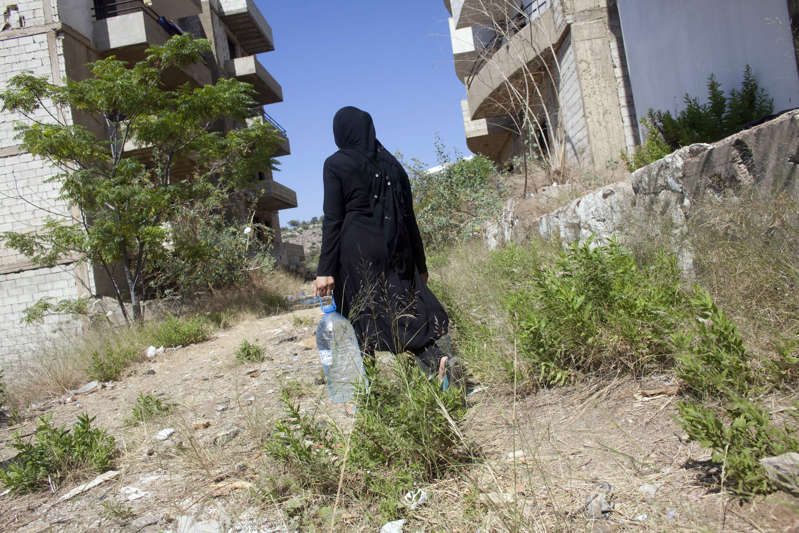 a man standing in front of a building: A Syrian mother collects water for cooking