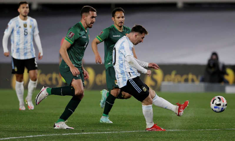 a group of people playing football on a field: Messi fires home his first goal against Bolivia. Photograph: Juan Ignacio Roncoroni/Reuters