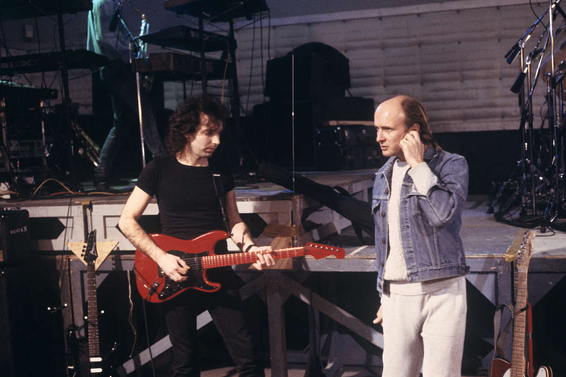 a man and a woman holding a microphone: Joe Satriani and manager Mick Brigden at SIR Studios in New York City on February 20, 1988. (Ebet Roberts / Redferns)