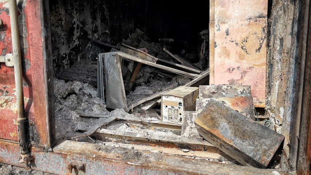 a broken brick wall: Burned out hard drives and documents are seen at the facility