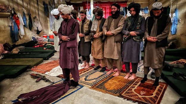 a group of people standing in front of a crowd: Taliban fighters pray inside the cells
