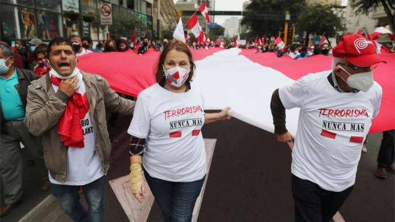 """a group of people standing in front of a crowd: Peruvians carrying banners reading """"Terrorism never again"""" marked the anniversary of Guzmán's capture"""