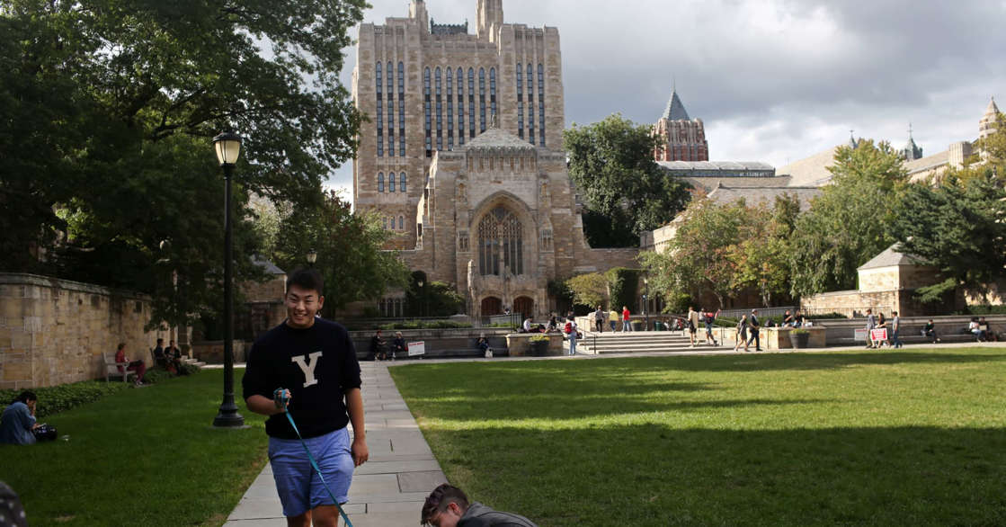 a group of people playing frisbee in a park: Yale University