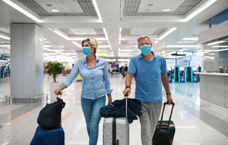 a person standing next to a bag of luggage: Middle aged couple at an airport during coronavirus pandemic.
