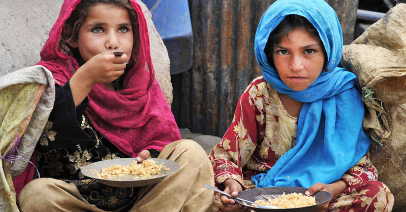 a little girl sitting at a table with a plate of food: Afghan children, who salvage recyclable items from garbage to make a living, eat a meal of rice in Jalalabad on June 30, 2013.