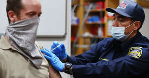 a man wearing a hat: Firefighter paramedic Cuevas (R) administers a Covid-19 vaccination dose to a person at a vaccination event at Culver City Fire Department Station 1 on August 05, 2021 in Culver City, California.