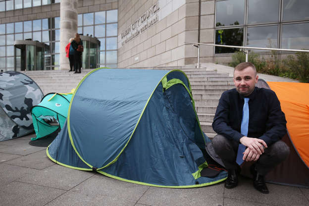 a person sitting in a tent: Councillor Anthony Flynn