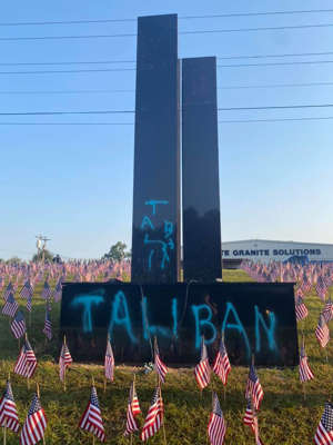 """a group of people on a field: A 9-11 memorial was vandalized outside a local business in Greenville with someone spray painting the words """"Taliban"""" on it, deputies say"""