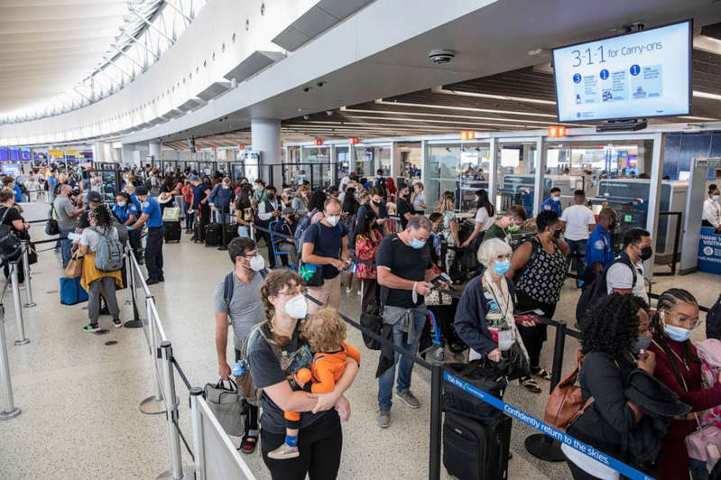 a group of people standing in front of a crowd: Passengers endure a long queue for security screenings at John F. Kennedy International Airport in New York, Aug. 19, 2021.