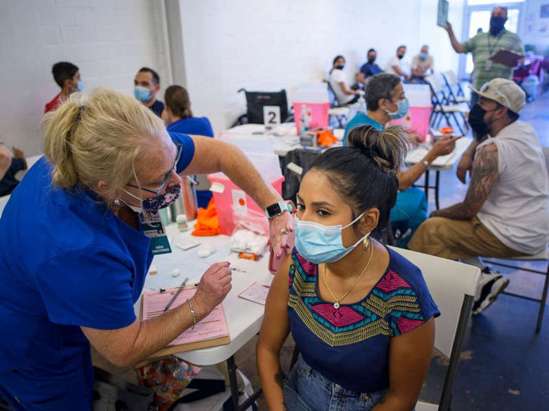 a group of people around each other: Raquel Gonzales, 27, receives a coronavirus vaccine during a free vaccination clinic in San Antonio, Texas, Sept. 11, 2021.