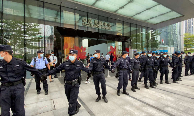 a group of people standing in front of a building: Security personnel form a human chain as they guard outside the Evergrande's headquarters, where people gathered to demand repayment of loans and financial products, in Shenzhen on Monday.