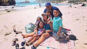 a group of people sitting at a beach: Daniel and Davy Macias with their four children. A fifth, a girl, was born after both parents were hospitalized for Covid-19.