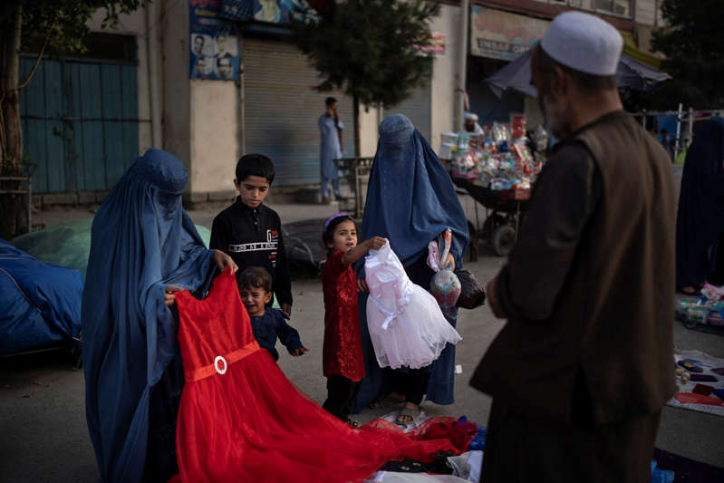 a group of people walking down the street: Afghan women and a girl shop for dresses at a local market in Kabul on Sept. 10, 2021.