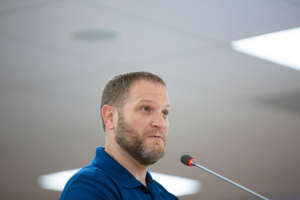 a man wearing a blue shirt: Maury County Commission Scott Sumners speaks before the MCPS school board regarding a new letter of intent for the construction of a bridge between Battle Schools in Spring Hill during a meeting at Horace O. Porter School on Sept. 9, 2019.