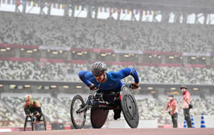 a man riding on the back of a bicycle: Vitali Gritsenko of Team RPC in the men's marathon T52 during the 2020 Tokyo Paralympics. Alex Davidson/Getty Images