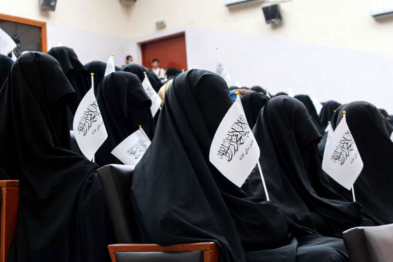 a group of people in a room: Afghan students listen to women speakers before their pro-Taliban rally outside the Shaheed Rabbani Education University in Kabul on Sept. 11, 2021.