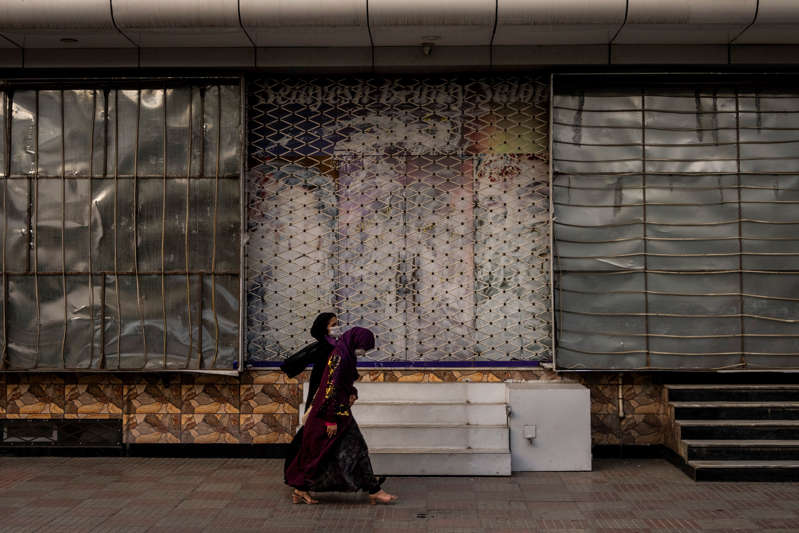 a person sitting in front of a building: Afghan women walk past a closed beauty salon in Kabul on Sept. 11, 2021.