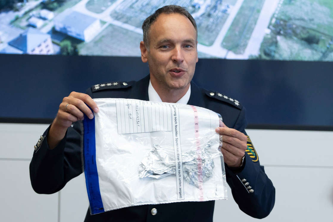 a man holding a microphone: Police spokesman Thomas Geithner shows the remains of the metal foil of a balloon during a press conference in Dresden, Germany, Tuesday, Sept 14, 2021 discovered in the substation Dresden-Sued (Dresden-South). German police are investigating the source of a balloon that caused a massive blackout Monday in and around the eastern German city of Dresden.