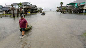 a person standing next to a body of water: Bubba Ferguson drags a kayak through a flooded street in San Luis Pass, Texas.