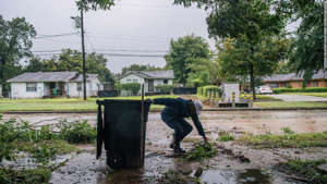 a person walking down a dirt road: Dallas Baines of Houston throws fallen tree branches into the trash.