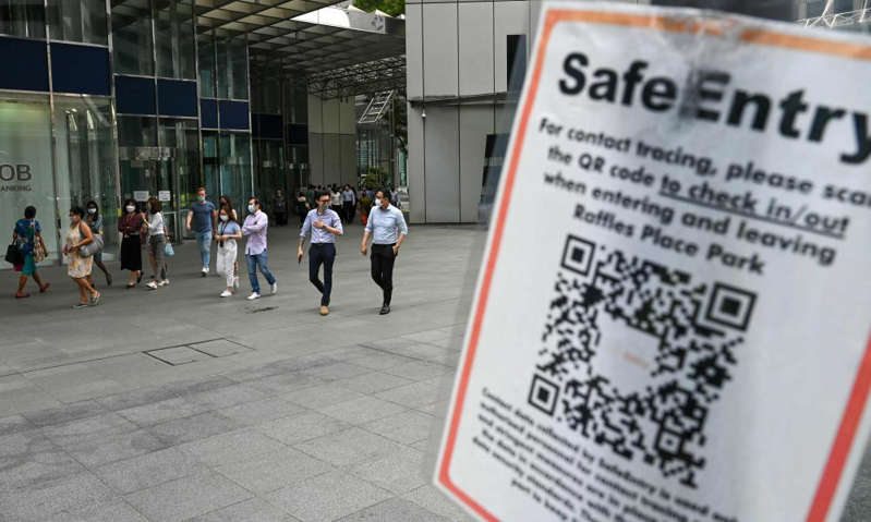 a person holding a sign: A Covid-19 coronavirus contact tracing sign is seen as people enjoy a lunch break at the Raffles Place financial business district in Singapore on Tuesday. Photograph: Roslan Rahman/AFP/Getty Images