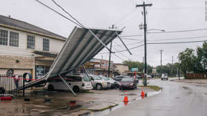 a car parked on a street: A carport hangs from power-lines after Tropical Storm Nicholas moved through the area on September 14, 2021 in Houston, Texas. Tropical Storm Nicholas strengthened to a Category 1 hurricane as it made landfall late Monday evening, but is gradually weakening as it moves towards the Northeast. Nicholas is projected to become a tropical depression by tomorrow.