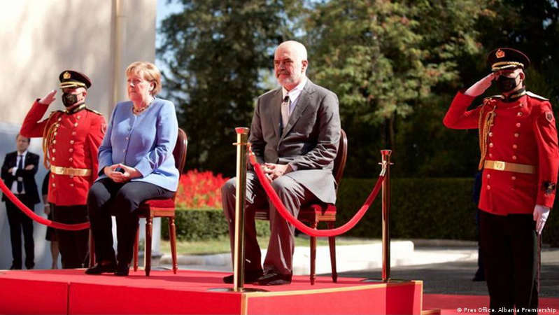 a group of people wearing costumes: Angela Merkel at a ceremony in Tirana with Albanian PM Edi Rama