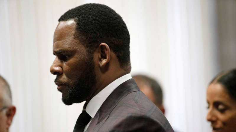 a man wearing a suit and tie: R Kelly denies the charges filed against him
