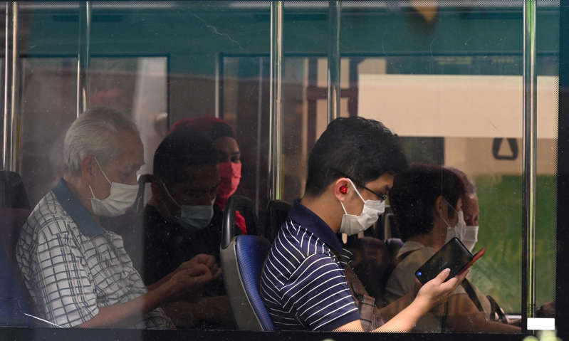 a group of people looking at a cell phone: People wear face masks on a public bus in Singapore. On Tuesday, the country reported 837 new Covid cases. Excluding children under 12, 90% of the population is vaccinated against Covid.