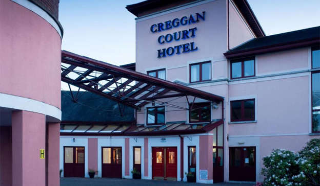 a large clock tower in front of a building: On Tuesday night, Jacub Kostanski went to sleep at the Creggan Court Hotel. Pic: Creggan Court Hotel
