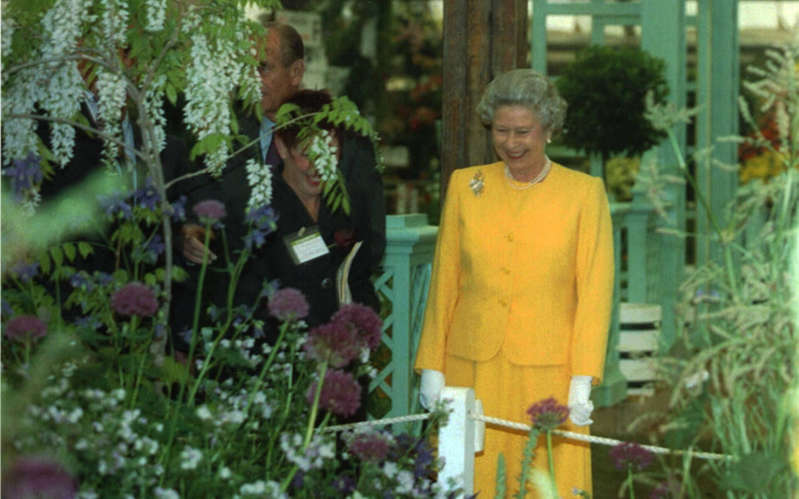 Elizabeth II standing in front of a flower: The Queen looks around exhibits at the Chelsea Flower Show in 1994 - PA