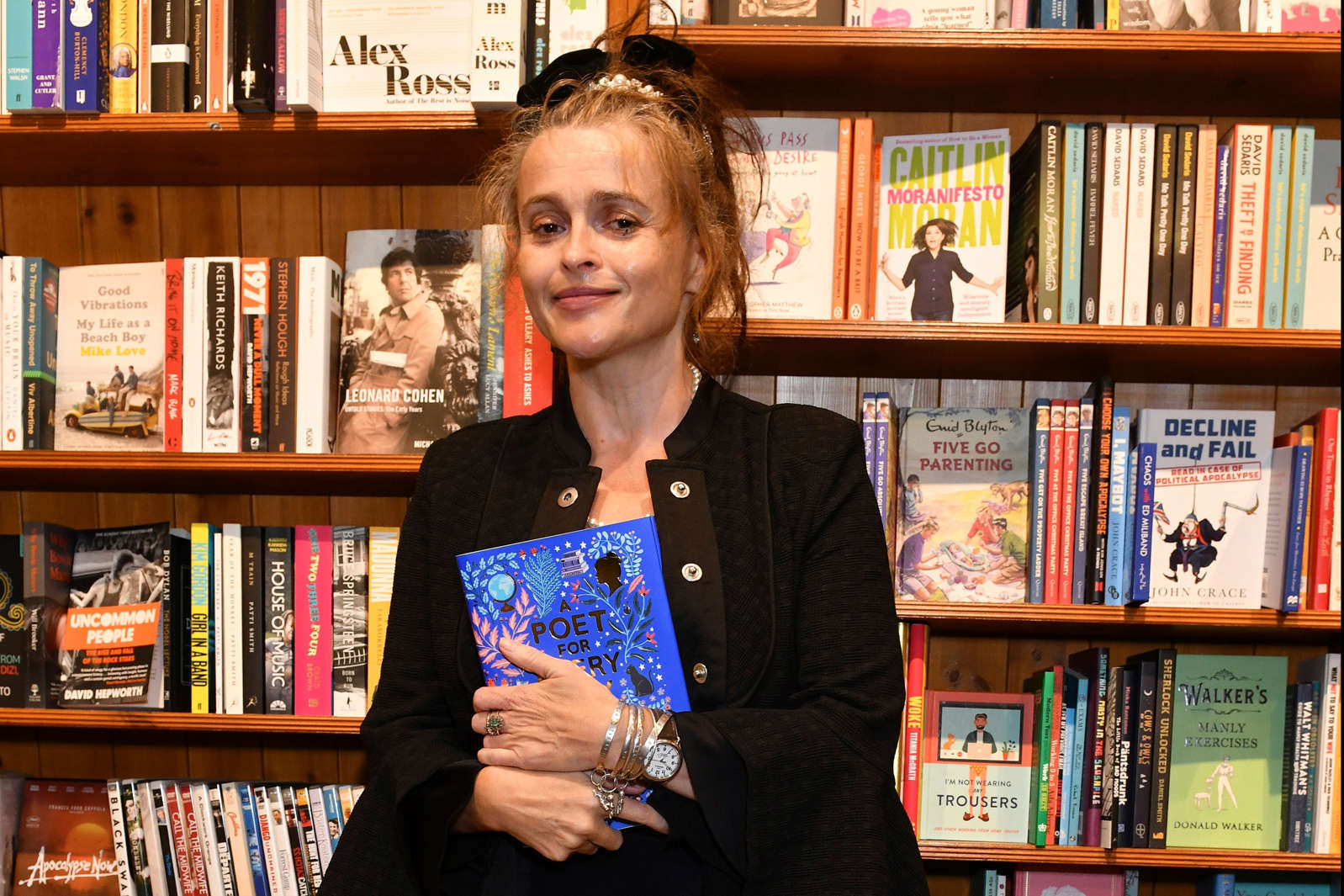 """Helena Carter reading a book in front of a bookshelf: Helena Bonham Carter attends the launch of new poetry anthology """"A Poet For Every Day Of The Year"""" by Allie Esiri (Dave Benett)"""