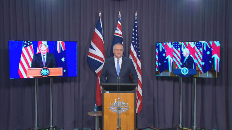a sign in front of a television: Prime Minister Scott Morrison announced the new defence pact in a joint virtual media conference with Joe Biden and Boris Johnson.
