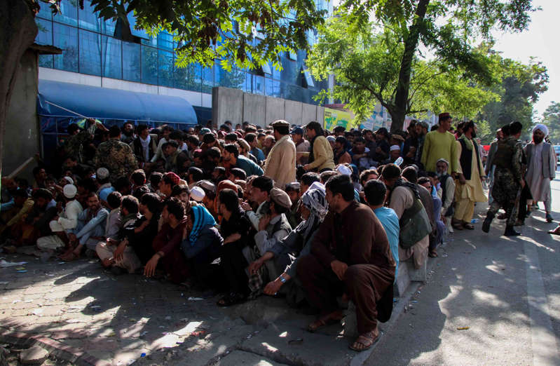 a group of people walking down the street in front of a crowd: People queue to withdraw money from a bank in Kabul, Afghanistan, on September12. EPA