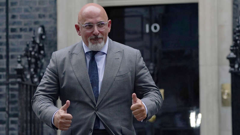 Nadhim Zahawi wearing a suit and tie standing in front of a building: Nadhim Zahawi appeared to be happy with his promotion