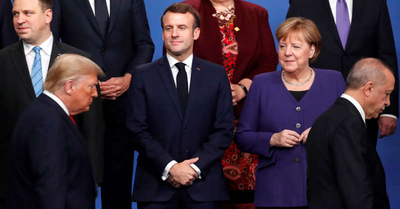 Jüri Ratas, Emmanuel Macron, Angela Merkel standing next to a person wearing a suit and tie: France's President Emmanuel Macron (2nd L) and Germany's Chancellor Angela Merkel (R) look at US President Donald Trump (front L) and Turkey's President Recep Tayyip Erdogan (front R) walking past them during a family photo as part of the NATO summit at the Grove hotel in Watford, northeast of London on December 4, 2019.