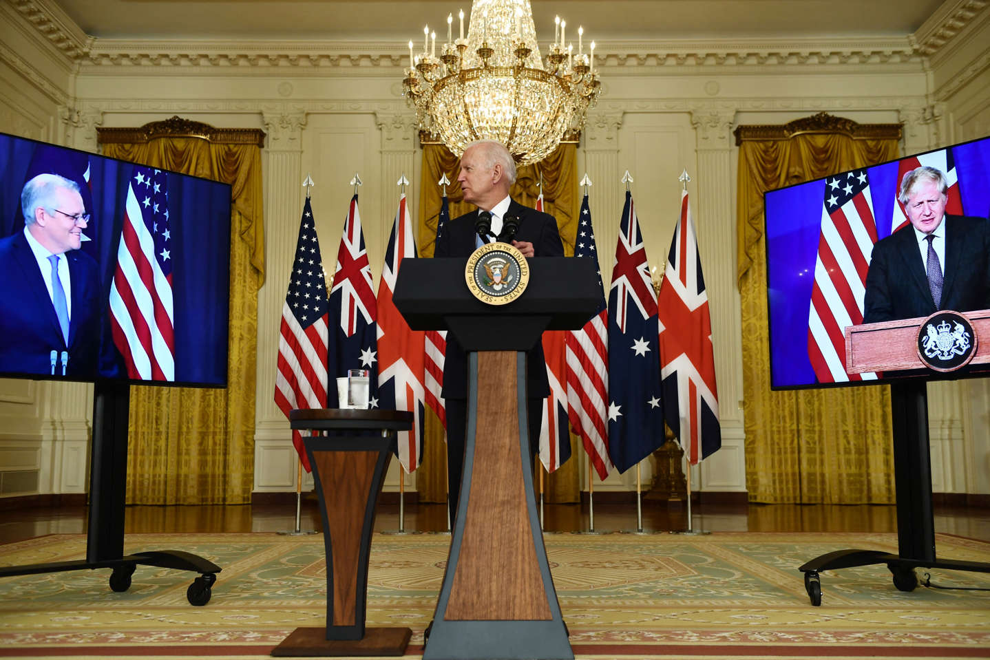 Boris Johnson et al. in a room: President Joe Biden participates in a virtual press conference to announce trilateral defense partnership AUKUS, with British Prime Minister Boris Johnson (R) and Australian Prime Minister Scott Morrison, in the East Room of the White House in Washington, D.C, on September 15, 2021.