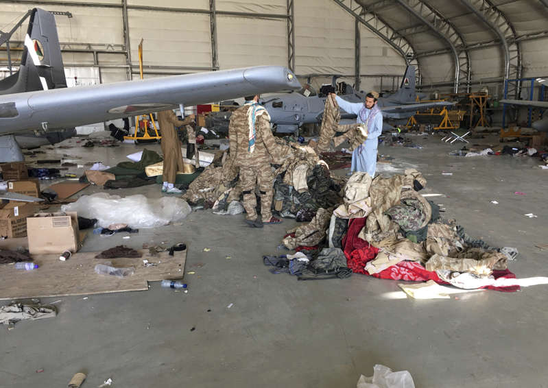 a group of people standing around a plane: Taliban fighters collect military clothes near damaged Afghan military aircraft after the Taliban's takeover inside the Hamid Karzai International Airport in Kabul, Afghanistan, Sunday, Sept. 5, 2021.